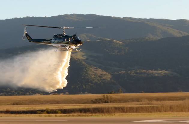 Pilots use Santa Barbara County's new state-of-the-art Copter No. 3 to demonstrate a water drop on Monday at the Santa Ynez Airport. (Gina Potthoff / Noozhawk photo)