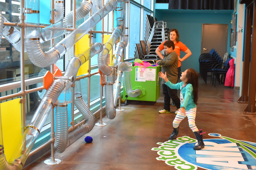 A young girl waits to catch a yarn ball as air shoots it from the Catching Air exhibit at the Santa Maria Valley Discovery Museum.