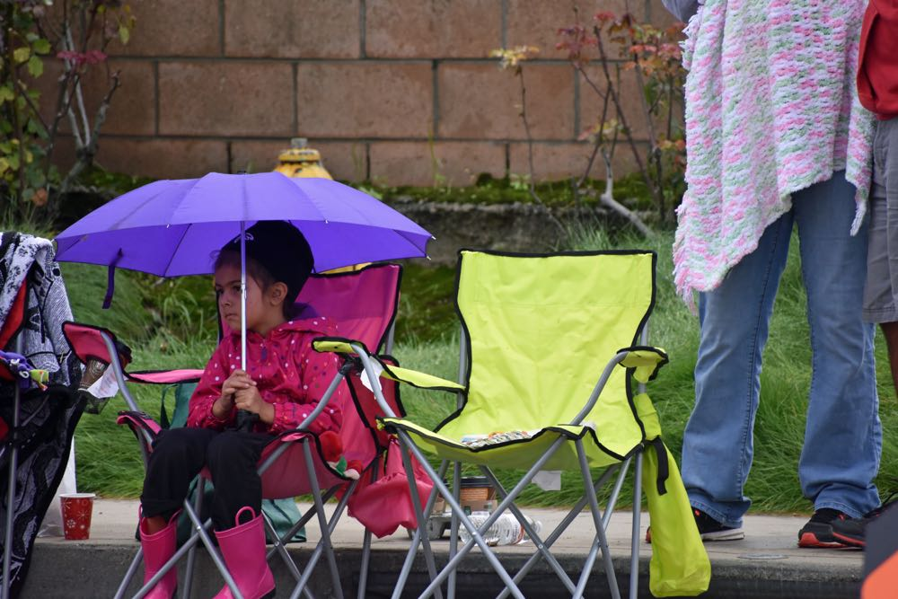 Equipped with an umbrella, galoshes and raincoat, a young parade fan awaits the start of the Old Town Orcutt Christmas Parade.
