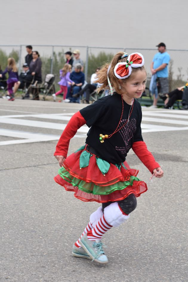 After handing out candy along the parade route, a young girl runs to catch up with her entry.