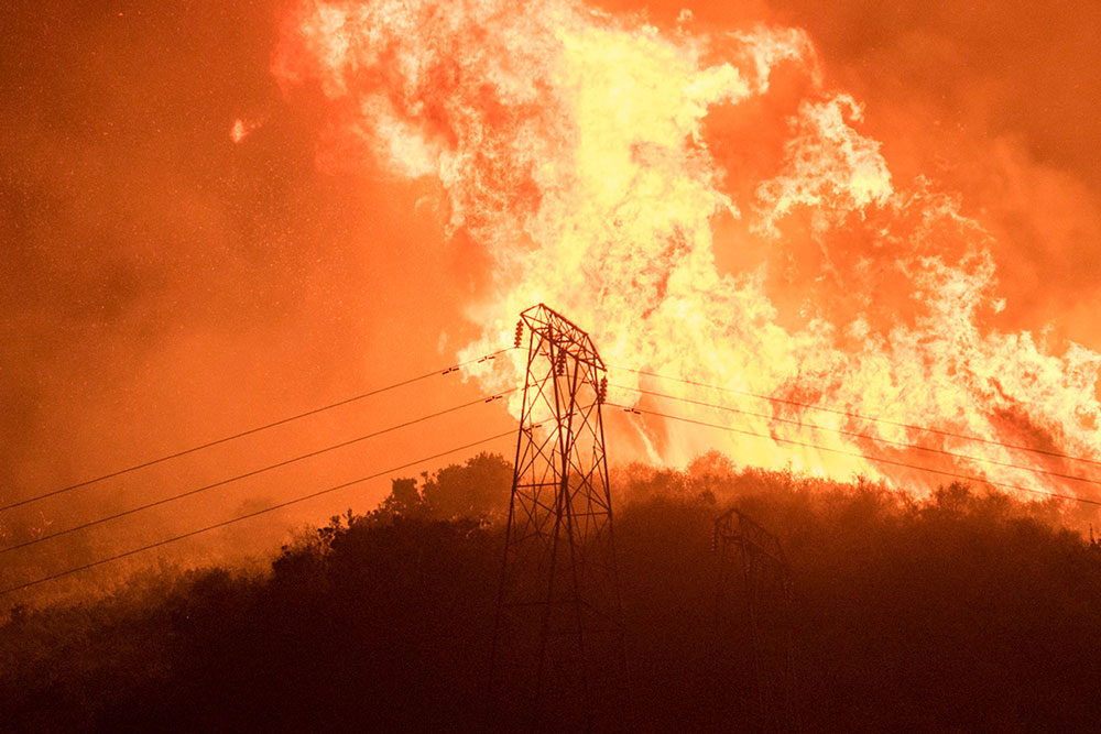 Flames from the Thomas Fire threaten high-voltage power lines last week near Carpinteria. SoCal Edison Co. officials are asking people to conserve electricity to help prevent future outages while the fire is stil burning.