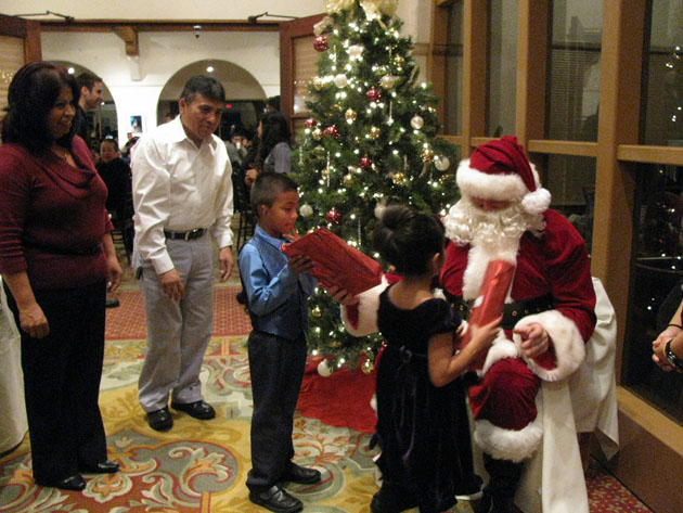 Jorge and Naomi Preciado, with parents Maria and Jorge, pay a visit to Santa Claus during Wednesday night's Police Activities League Holiday Dinner at the Cabrillo Arts Pavilion. (Giana Magnoli / Noozhawk photo)