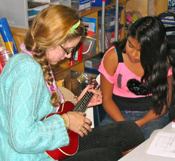 Selena Ross, left, a UCSB student and the M.U.S.I.C. Club's co-president and site coordinator at Isla Vista Elementary, works on math and ukulele with Jasmine. (George Foulsham photo)