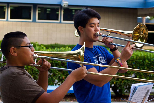 <p>UCSB alumnus David Lee, executive director of the M.U.S.I.C. Club, mentors Cristian from El Camino Elementary on trombone.</p>