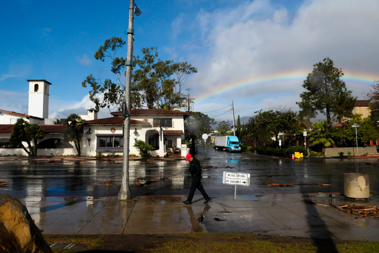A pedestrian walks down Cabrillo Blvd. on Friday as a rainbow breaks through the clouds.