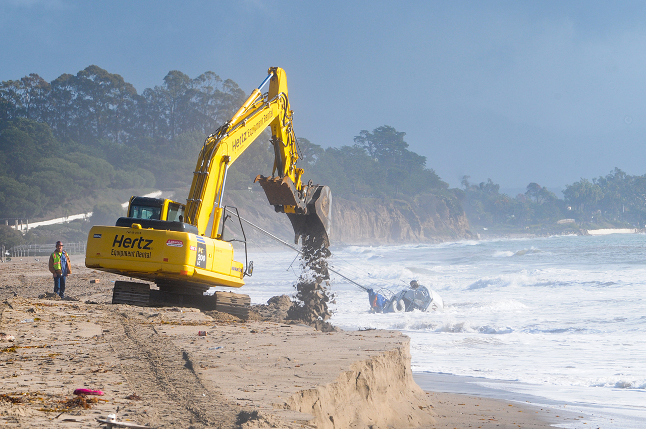 Crew works to cover exposed pipes with sand on Friday.  A sailboat had washed up behind them on the East Beach shore.