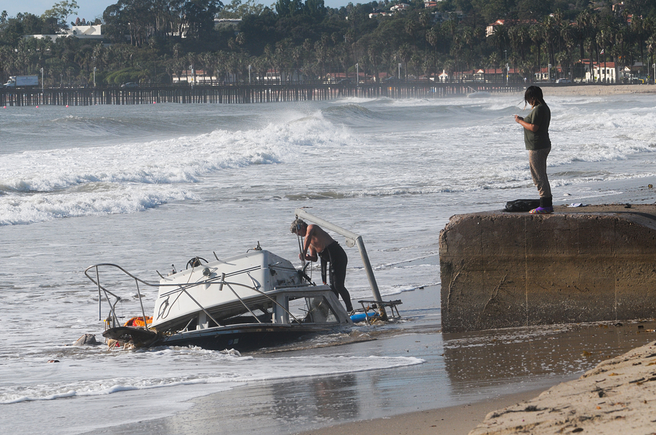 Waves crash around a boat that washed ashore Friday.