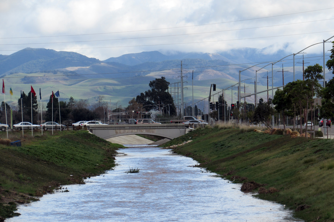 Vehicles travel Friday morning on Blosser Road in Santa Maria as water flows in a flood control channel  underneath them.