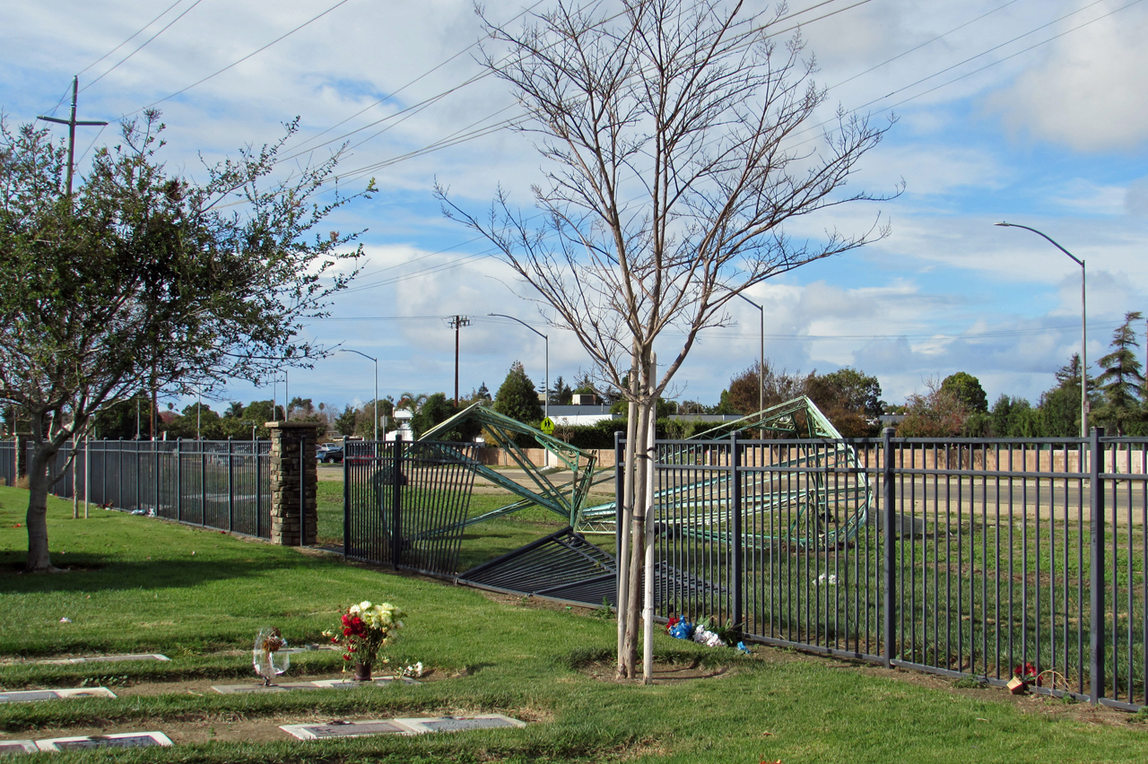 A shelter used over grave sites during services is crumpled and it apparently blew through the fence at the new section of the Santa Maria Cemetery, south of Battles Road.