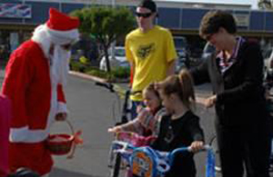 Santa helps give away bikes to children at Vandenberg Air Force Base. (PODS photo)