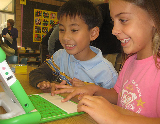 Third graders in D.J. Perry's class at Kellogg School get their first look at the XO laptop offered by One Laptop Per Child — and appear to like what they see.