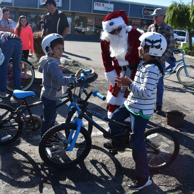 Caleb, 10, and Samuel Lopez, 7, talk to Santa Claus while sitting on their new bikes, courtesy of the Village Dirtbags program for children of deployed military members at Vandenberg Air Force Base.