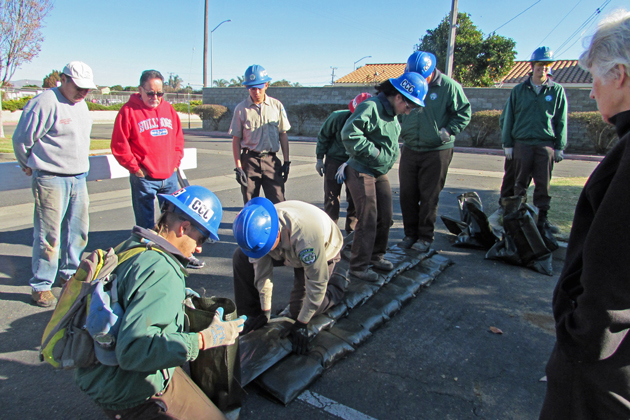 California Conservation Corps members demonstrate for Santa Maria residents how to use sandbags to build a structure to fend off flooding.