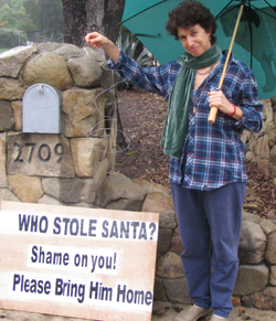 Evelyn Jacob, with her sign pleading for Santa's return, says her homemade decorations are among her many labors of love.