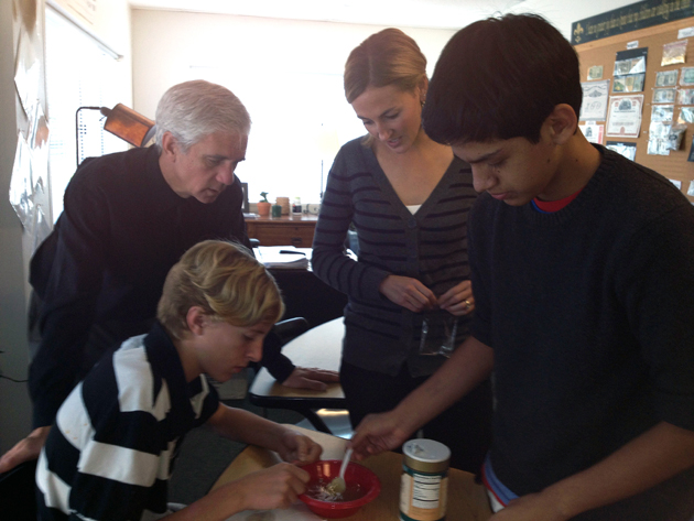 Providence Hall humanities teacher Bruce Rottman and science teacher Laura Schultheis help freshman students learn about ancient Roman coins by using the principles of electrolysis to clean the coins. (Providence Hall photo)