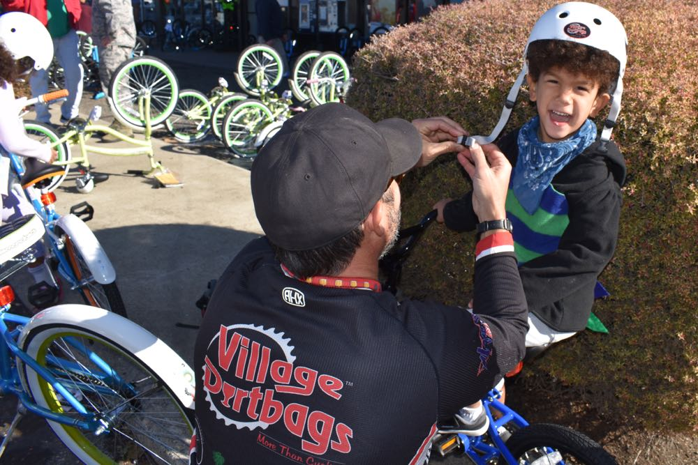 Roderick Rockwood, 4, sports a broad grin while getting fitted for a helmet to go with his new bicycle.
