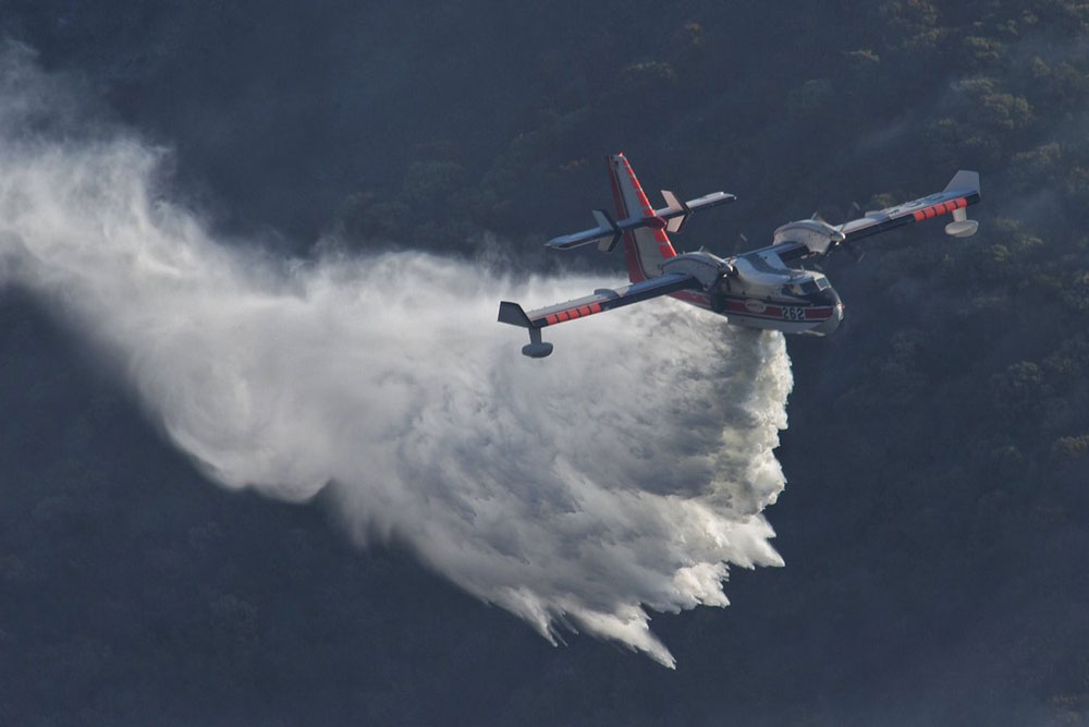 A Bombardier 415 Superscooper makes a water drop Sunday on hot spots along the hillside east of Gibraltar Road as the Thomas Fire burns into its 14th day. Calmer conditions are allowing firefighters to go on attack against the stubborn blaze.