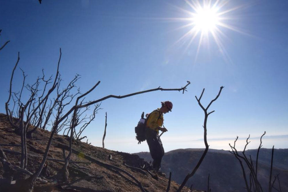 Santa Barbara County Fire Capt. Ryan Thomas hikes down steep terrain below East Camino Cielo on Tuesday to meet with his crew and root out and extinguish smoldering hot spots on the Thomas Fire. Incident commanders were expressing confidence their crews could keep the blaze in check in the face of high winds expected Wednesday night.