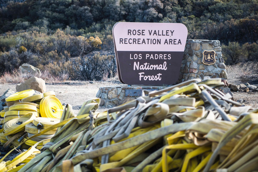 Hoses used to the battle the north flank of the Thomas Fire in the Rose Valley area north of Ojai are gathered up for repair and reuse. The blaze had blackened 273,400 acres as of Friday night, making it the largest wildfire in recorded history in California. It remained at 65% contained.