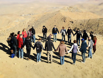 Friends form a prayer circle at a cliff's edge on Government Peak, where Santa Barbara residents Daniel Carbonaro and Chris Rice crashed their ATV on Dec. 18.