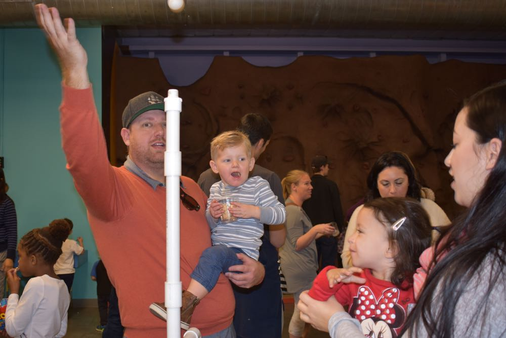 A family plays with the air-launched ball exhibit at the Santa Maria Valley Discovery Museum.
