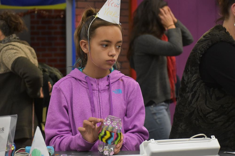 Amaya Martinez, 11, contemplates her next addition for her colorful noisemaker.