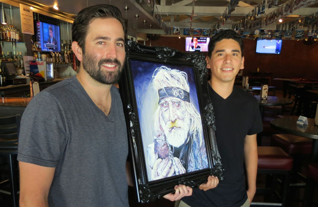 Derek Guilin, left, and Jason Rio Hernandez have worked in the Santa Barbara service industry as servers and bartenders for several years and are hoping to capitalize on that fact by founding the Will Rise Project, a company and brand meant to highlight the work of local artists. The pair holds up its Will Rise logo, a portrait of a homeless man drawn by Hernandez.