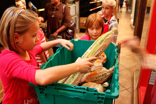 <p>Girl Scouts and sisters Anastacia and Natalie Fenker help load a cart with groceries for a shopper Saturday at Unity Shoppe.</p>