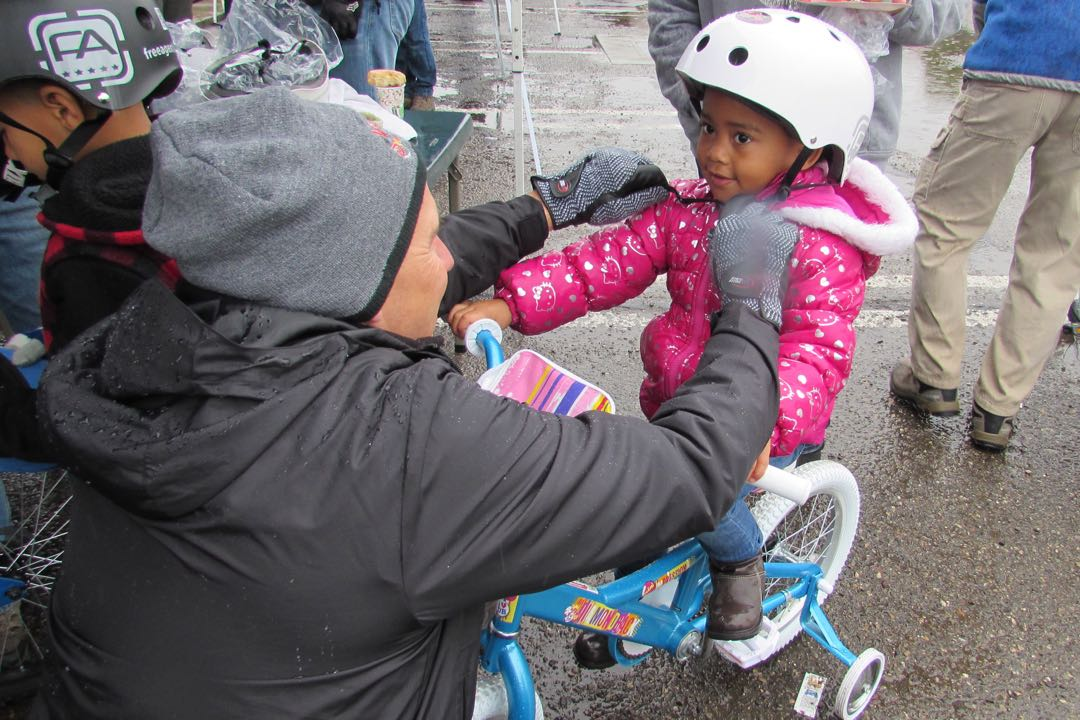 While perched on her new bicycle, 3-year-old Nyah Ingram has her helmet adjusted by Randy Baumgardner, who was working with the Village Dirtbags on Saturday in Lompoc. The group of mountain-biking enthuasiasts delivered 120 bikes during the 10th annual event.