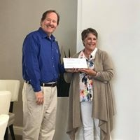 Derek Hansen, vice president of development construction at The Towbes Group, presenting Women's Fund of Northern Santa Barbara County representative Diane Adam with an investment from an employee group.