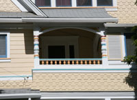 Detail of a Queen Anne Revival house with fanciful shingles, siding and turned posts.