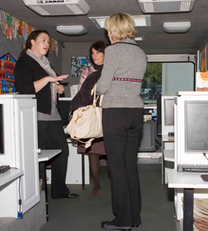 Mobile Waterford teacher Mary Elena explains to Women's Fund members how children are taught English in the program so they can enter kindergarten prepared to learn. The Women's Fund contributed $95,000 to enable the Mobile Waterford van to bring computers and software to 4 year olds and their parents in the neighborhoods where they live.
