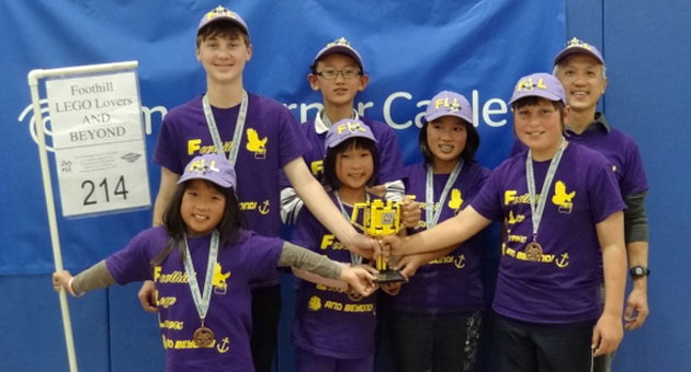 The Foothill LEGO Lovers AND BEYOND! team and their coach flash championship smiles after claiming second place in the FIRST Lego League Los Angeles Regional Championship Tournament. (Sylvin Chou photo)