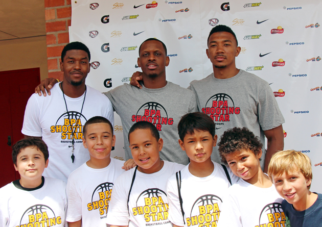 NBA players Julyan Stone, James Nunnally and Orlando Johnson with camp participants.