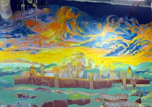 This mural of a city on a hill is painted on a wall in the warehouse of Twenty Four 7 Moving Specialists in Goleta. Owner Brett Menth says the artwork depicts the spiritual beliefs that prompted him to buy a facility to store clients' valuables. (Gina Potthoff / Noozhawk photo)