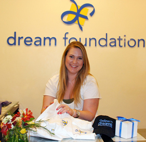 All in a day's work for Dream Foundation office manager Rachel Stelle: Folding T-shirts and gathering badges, baseball caps and cups for dream recipients and family members.