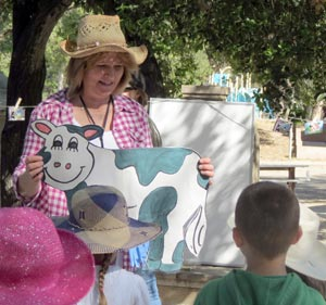 Independent Study program teacher Susan Degner leads her kindergartners in a farm-themed song before they dig into dishes prepared by their parents for a recent Farm Festival at Pioneer Park in Santa Maria. (Gina Potthoff / Noozhawk photo)