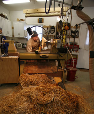 A pile of shavings isn't just debris. Chris Hansen uses the wood strips to slow down the drying process for his hand-turned wooden bowls.