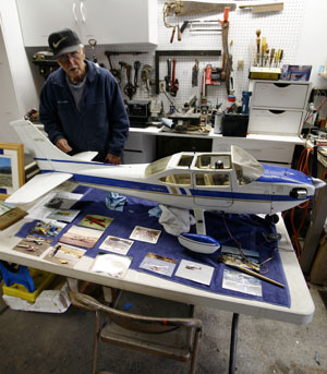 John Fodor, from inside his garage workshop, counts down to takeoff time with one of his model airplanes.