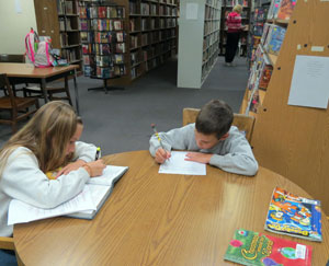 Alex Thompson, left, and her brother, Caleb, do homework at the old Orcutt branch library, which was located at the Oak Knolls Shopping Center. (Gina Potthoff / Noozhawk photo)