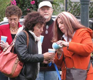 Adelante Charter School principal Juanita Hernandez, right, helps Glendon Association's Jina Carvalho light a candle at Saturday's vigil for school massacre victims in Newtown, Conn. Standing behind them to the left are Santa Barbara County District Attorney Joyce Dudley and her husband, John Dudley. (Giana Magnoli / Noozhawk photo)