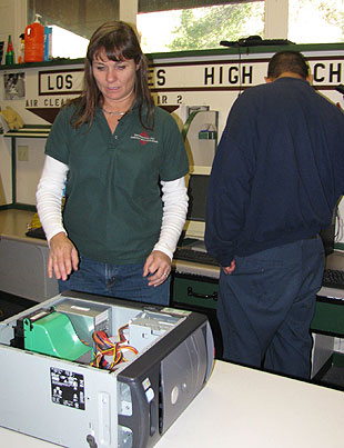 Melanie Sutton, who teaches computer classes and oversees the Computers for Families program, helps new students take apart, fix and program donated desktop computers.