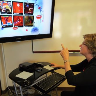 Debra Lieberman, director of UCSB's Center for Digital Games Research, shows off examples of some cancer-related games that teach users about the importance of white blood cells and ways to battle the disease. (Gina Potthoff / Noozhawk photo)