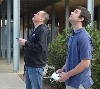 DPNews teacher John Dent, left, and student operator Brett Williams keep an eye on the sky during a recent drone flight over the Dos Pueblos High campus. (Giana Magnoli / Noozhawk photo)