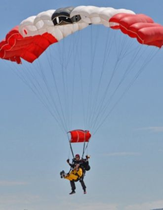 Lorin Brown comes in for a landing with his tandem partner, completing a jump to mark his 100th birthday. (Frank Cowan / Noozhawk photo)
