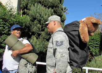 Carlos Madrigal, left, was accompanied by Air Force Tech. Sgt. Ubaldo Barrios, who toted bags of goodies and a giant stuffed bear that had been given to the veteran. (Janene Scully / Noozhawk photo)