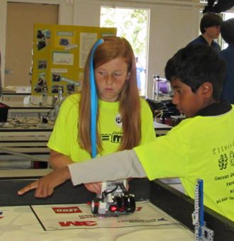 Ellwood School robotics team members Daphne Maskrey and Vinesh Manian test out the Goleta school's robot at the FIRST Lego League tournament. (Janene Scully / Noozhawk photo)