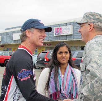 Roger McConnell, left, who leads the Village Dirtbags bike giveaway, greets Air Force Col. Keith Balts, commander of Vandenberg Air Force Base's 30th Space Wing. (Janene Scully / Noozhawk photo)