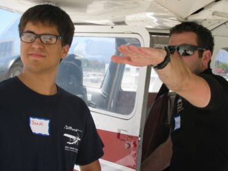 Above All Aviation flight instructor Patrick Corrigan, right, shows A Different Point of View student Joseph Monarres, 18, the proper way to judge wind direction and how to use wing ailerons to turn the plane while in the air. (Shaun Kahmann / Noozhawk photo)