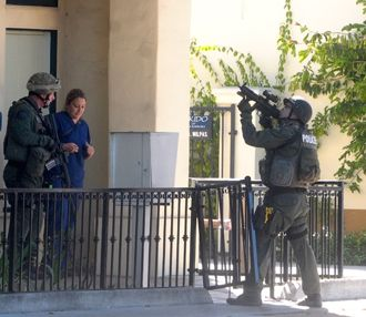 As Santa Barbara police SWAT members evacuate a Milpas Street medical clinic in 2011, one team member keeps watch on a second-story apartment where a gunman had been reported. There were no injuries in the incident. (Lara Cooper / Noozhawk file photo)